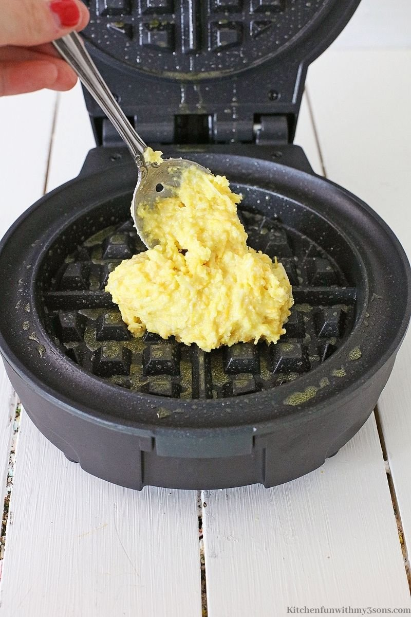 Adding the waffle mix to a grease waffle iron.