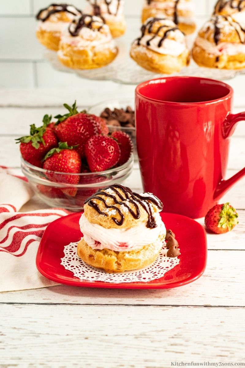 Cream puff on a small red serving plate with a red mug.