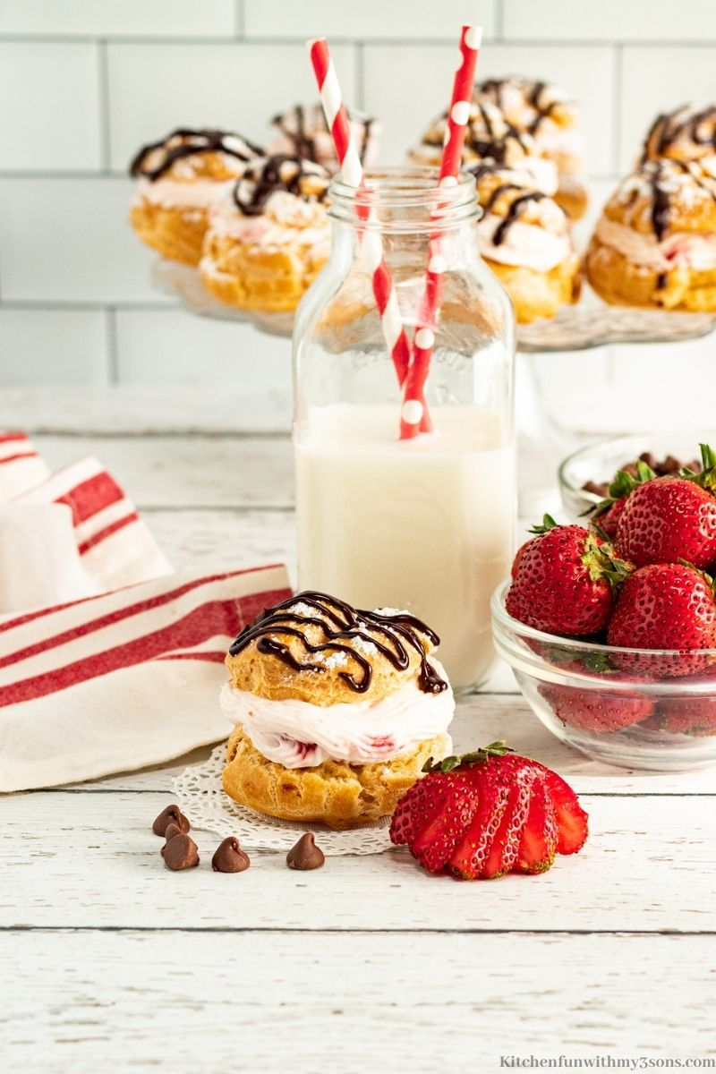 Cream puff with a glass of milk with two straws.