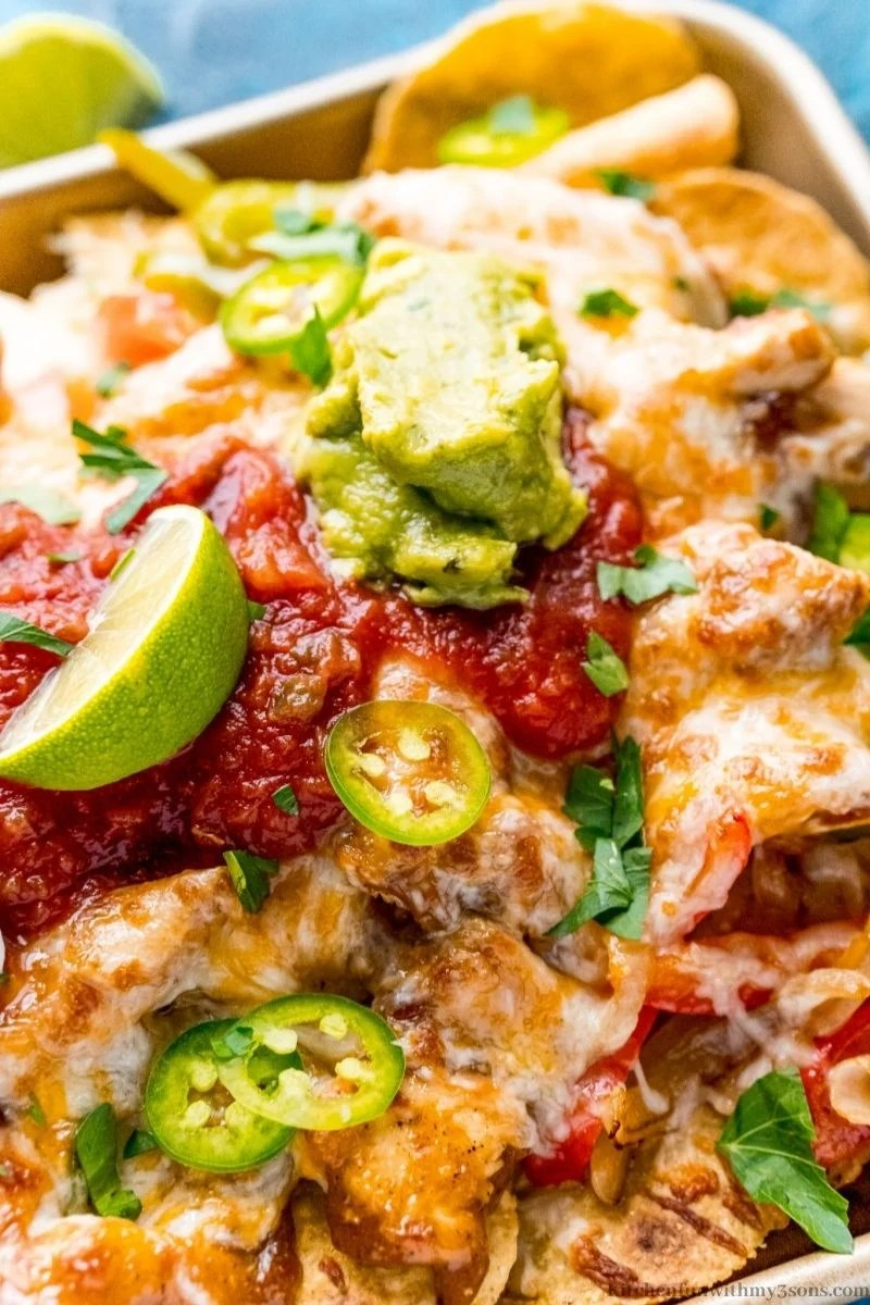 Nachos with lime wedges and guacamole.