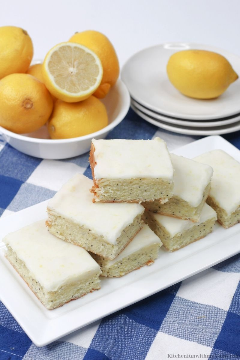 Lemon Poppy Seed Bars on a blue and white checkers cloth with extra lemons around them.