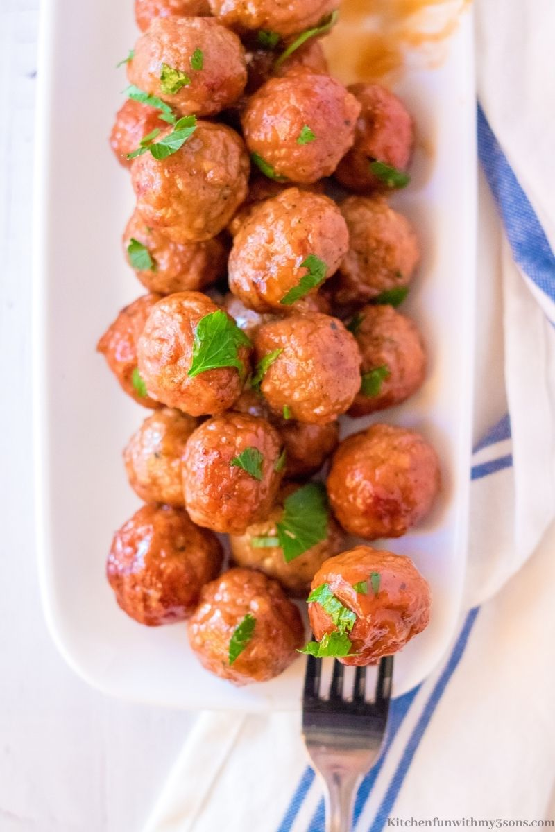The meatballs on a platter with a white cloth next to it.