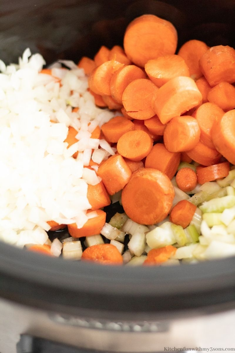 Adding the veggies into the slow cooker.