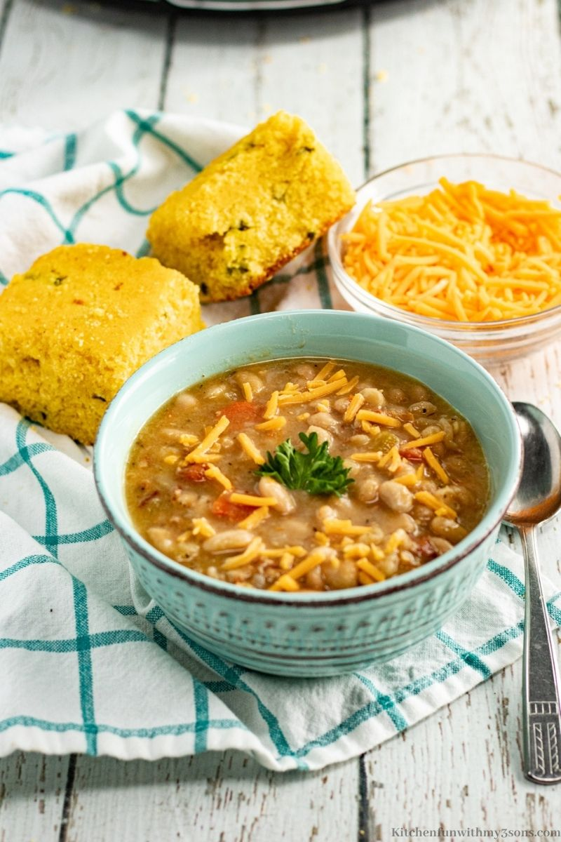 The Best Bean and Bacon Soup Recipe with a side of bread and more cheese.