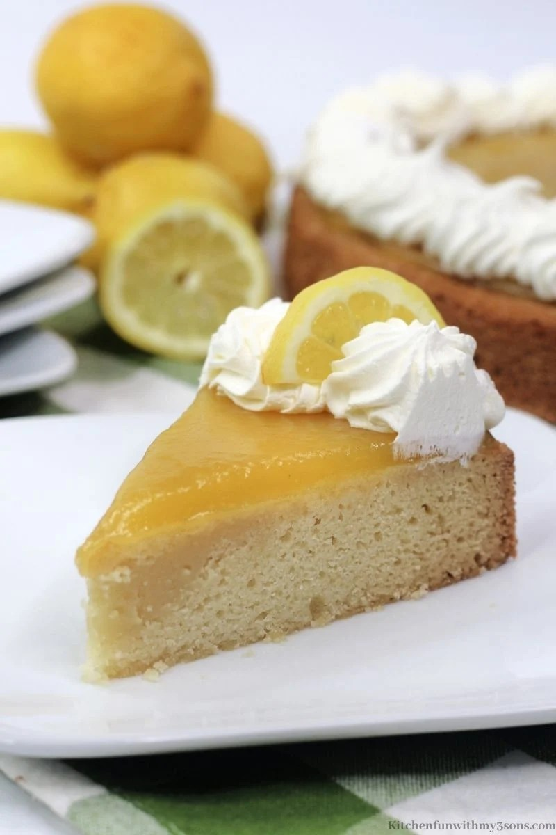 A piece of the lemon curd cake with a lemon wedge.