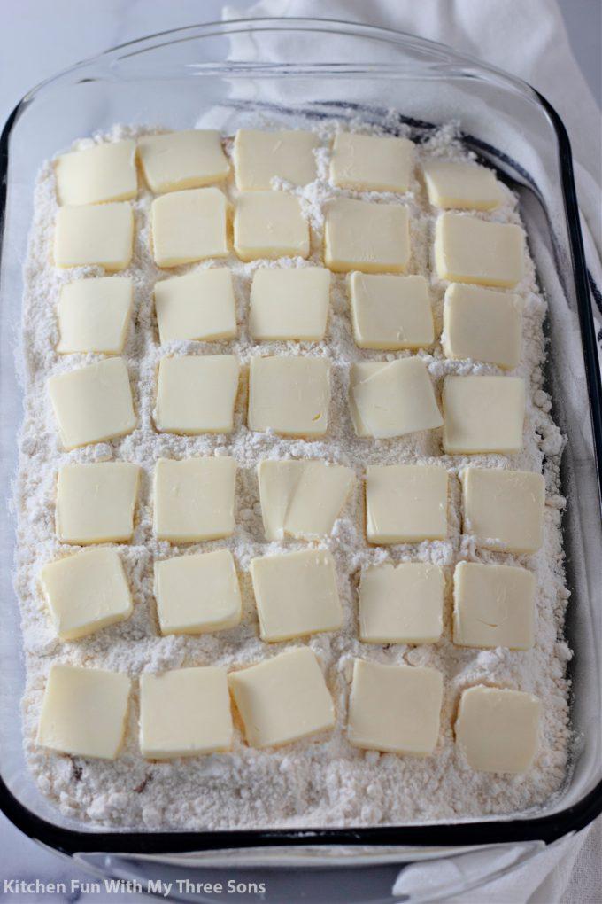 dodajući mazlice maslaca na vrh odlagališta kolača.