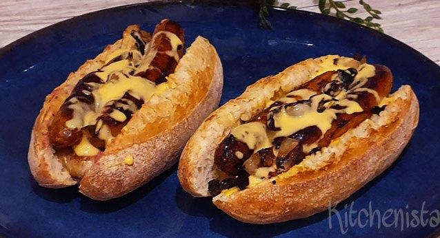 Hotdogs met geroosterde uien, groene peper en cheddar