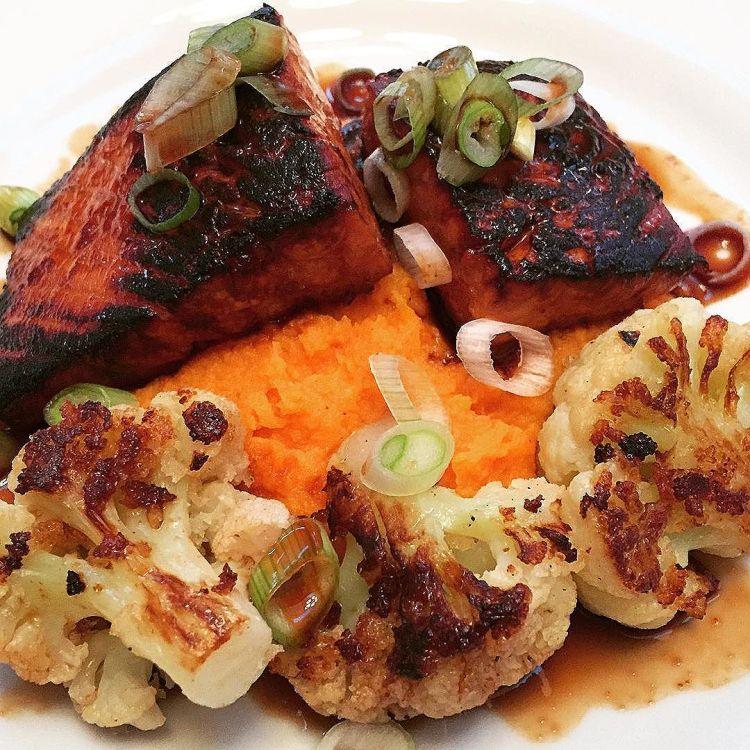 Honey Sriracha Salmon over smashed sweet potatoes with pan seared panko cauliflower florets.