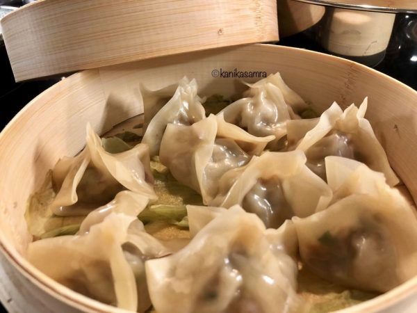 Bamboo steamer with cooked dumplings.
