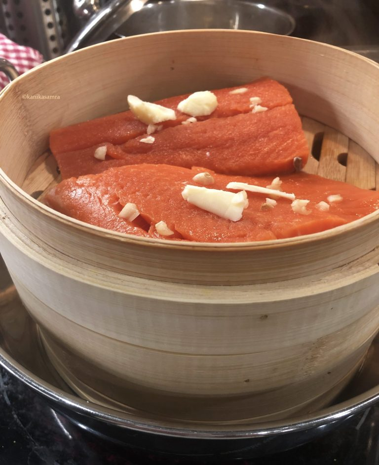Steamed salmon cooking in a bamboo steamer