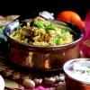 A pretty copper bowl full of Mutton Biryani served with Onion Raita