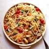 Platter full of noodles, garnished with cherry tomatoes, herbs and chilli flakes