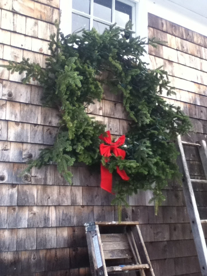 Mr. 46 makes a large Christmas wreath every year, strews it with little white lights, a red bow and affixes it to the front of our barn.