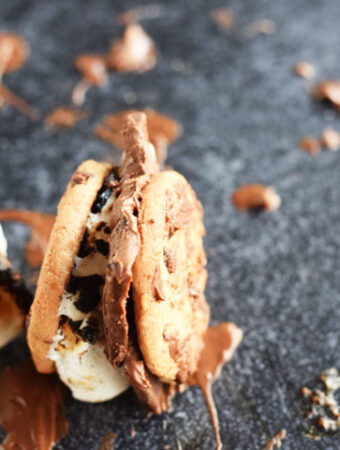 two chocolate chip cookies sandwiched with toasted marshmallow and chocolate