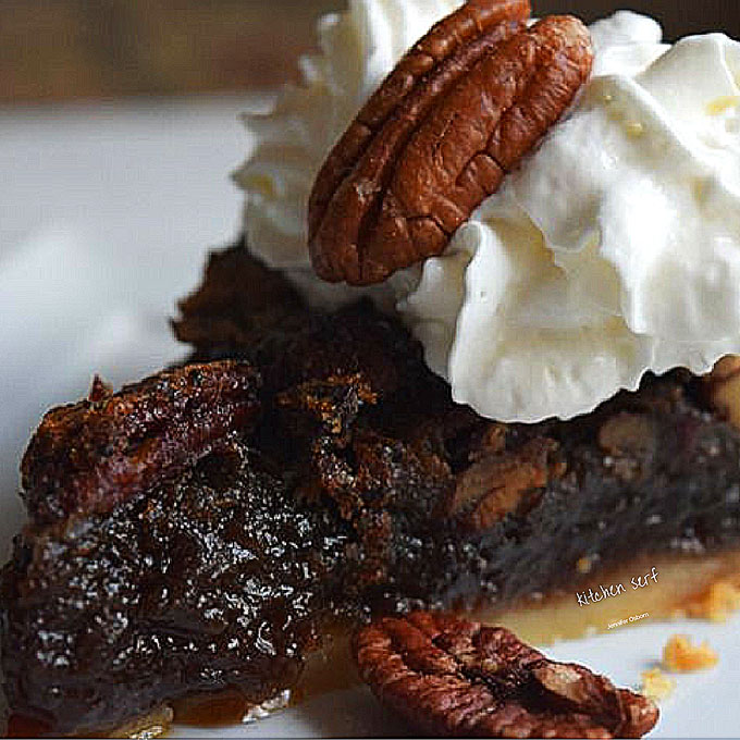 slice of pecan pie with whipped cream on a plate