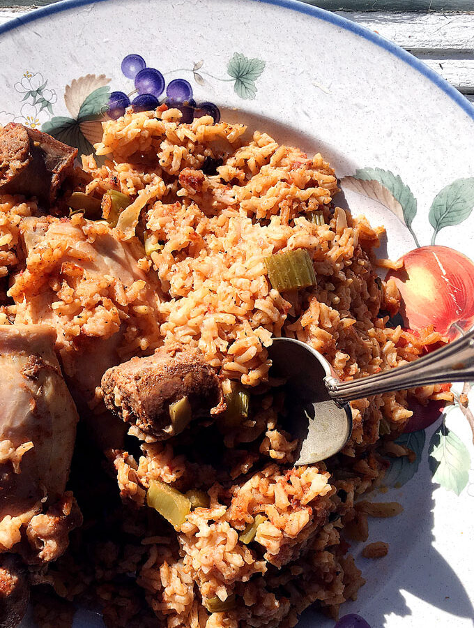 Dish and spoon with rice, chicken and sausage