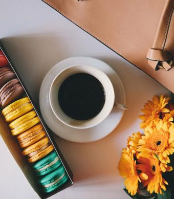 box of colorful macarons with a cup of coffee