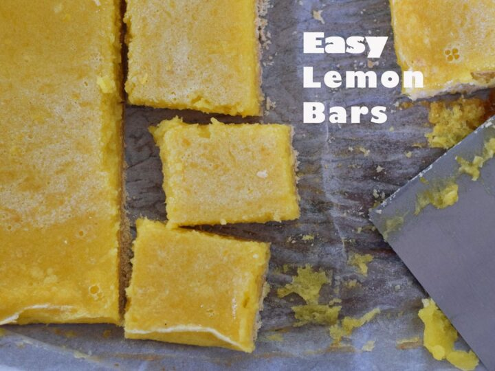 lemon bar squares on a piece of wax paper with a metal bench scraper next to it