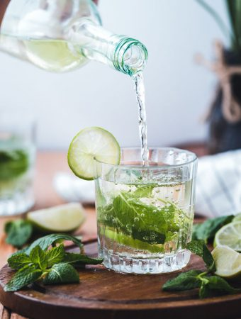 clear glass full of liquid on round brown board with slices of green lime and clusters of mint leaves around the glass