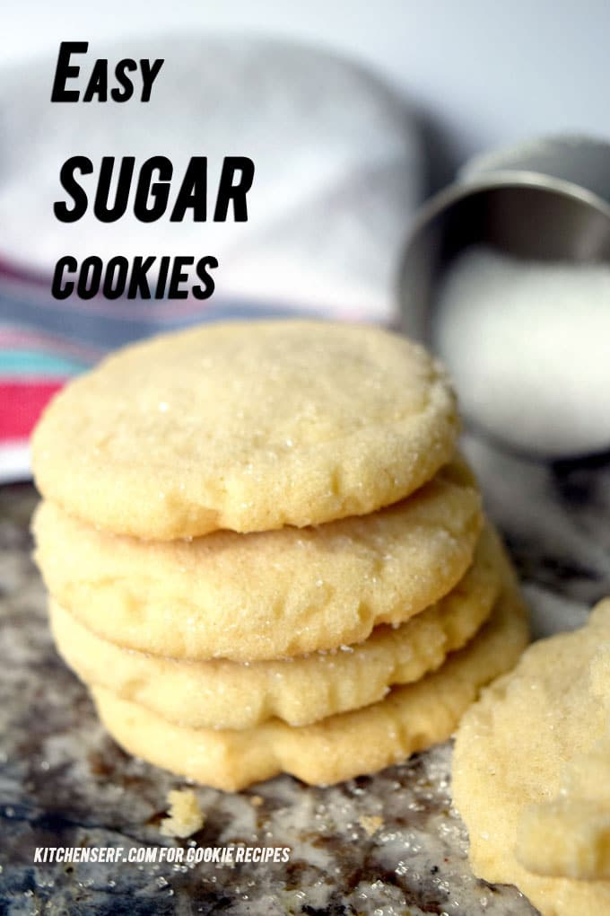 stack of sugar cookies with measuring cup of sugar and kitchen towel