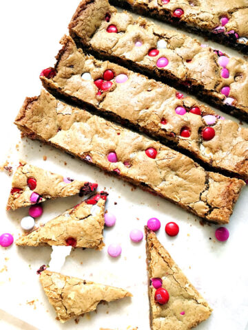 red, white and pink M&M's candy cookie bars in rectangles and triangles on a white background