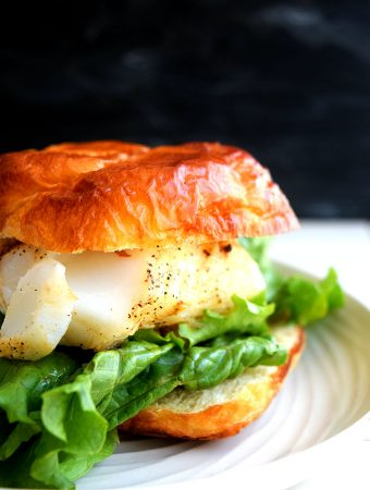 a fish fillet on a toasted bun with lettuce leaves on a plate on a white background