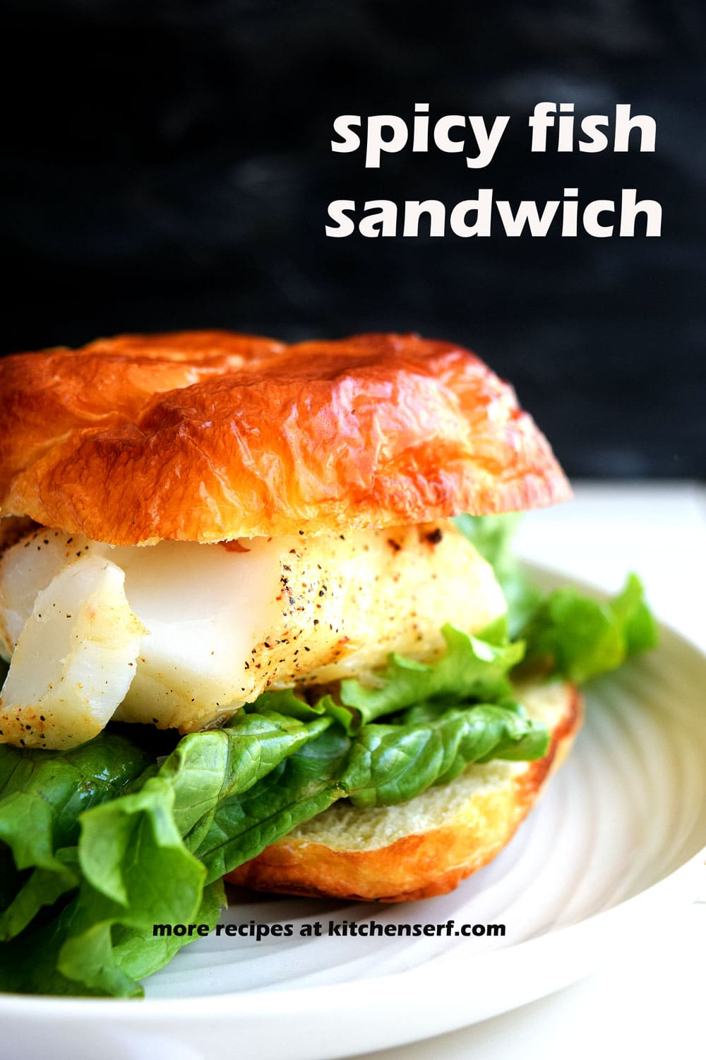 fish sandwich with lettuce leaves on off-white round plate