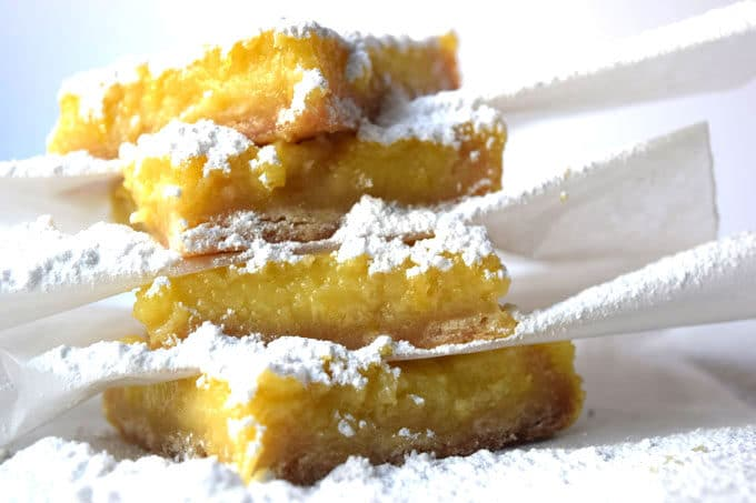 lemon bars covered with wax paper showered with powdered sugar, divided with squares of wax paper