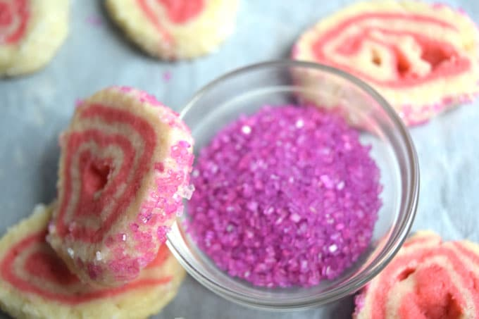 pink and white sugar cookies on a white backdrop with a tiny glass bowl of pink sanding sugar