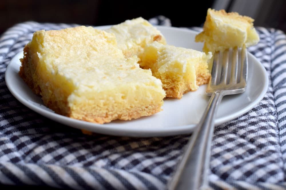 gooey butter cake slice on a white plate with a silver fork and a black and white checked cloth