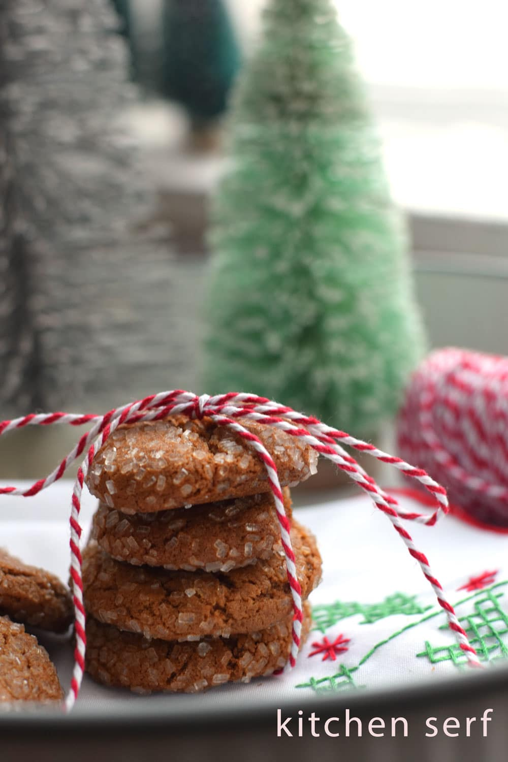 a stack of gingersnap cookies tied with red and white bakers twine on a white background with a bit of red and green cross stitching