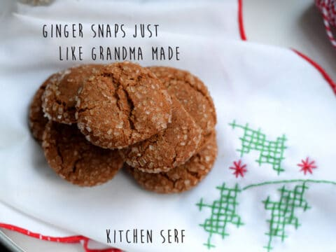 a stack of gingersnap cookies on a white cloth napkin with red trim and green and red cross-stitching
