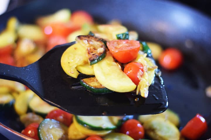 sauteed squash, tomatoes and zuchini on a spatula over a skillet