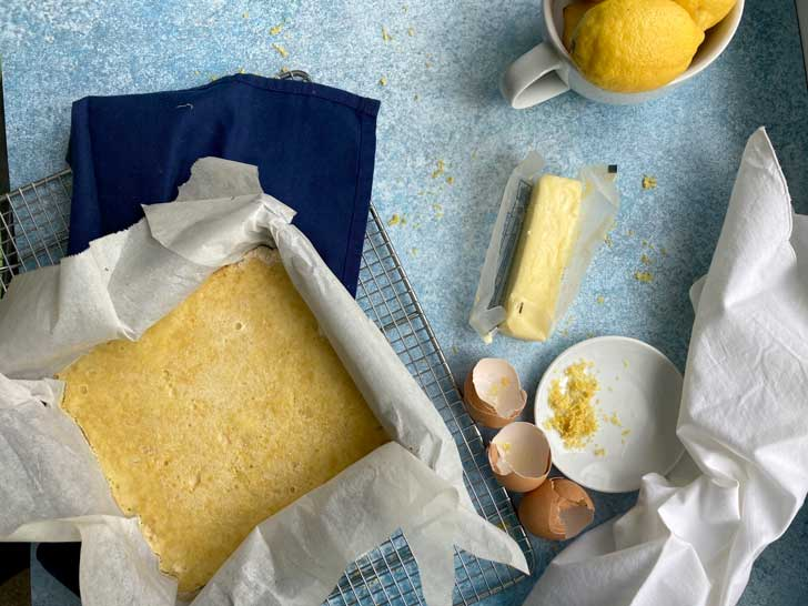 a pan of lemon bars on a blue background with a stick of butter, eggshells and lemon zest