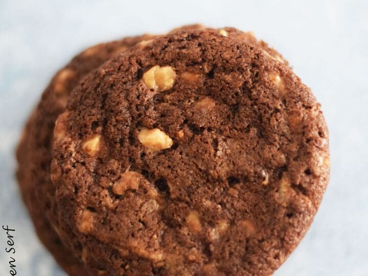 a chocolate toffee cookie on a pale blue background