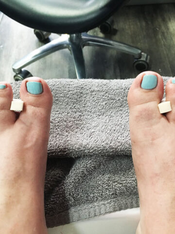feet resting on foot stool at nail salon