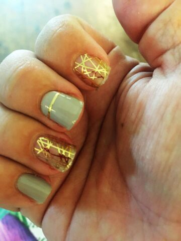 fingers wearing gold and gray nail stickers