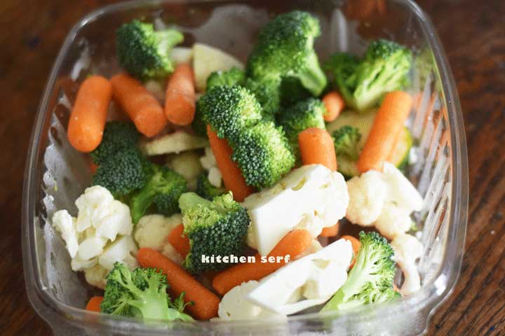 broccoli and cauliflower chunks with baby carrots in a plastic dish
