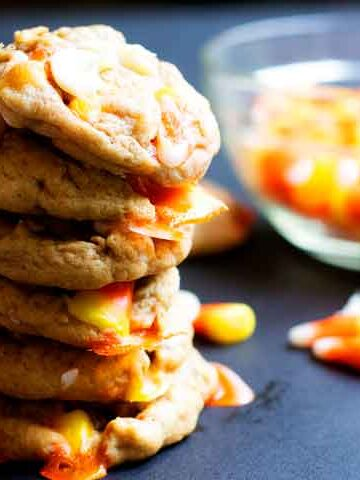 stack of white chocolate candy corn cookies next to a glass bowl of candy corn