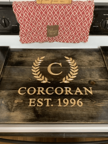 wooden stove top cover with engraving of a C the name Corcoran and established 1996 year