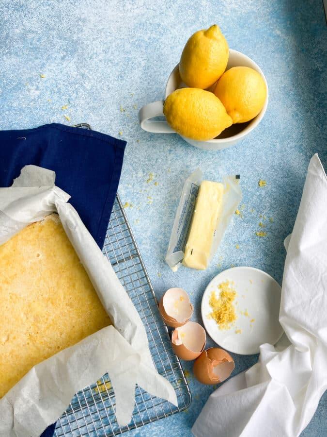 lemon bars cooling on wire rack next to egg shells, lemon zest, a bowl of lemons and a stick butter