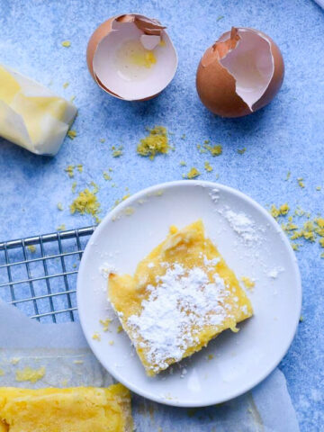 emon bar slice covered with powdered sugar on a baking rack next to eggshells and butter