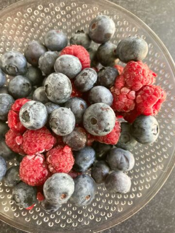 blueberries and raspberries in glass bowl