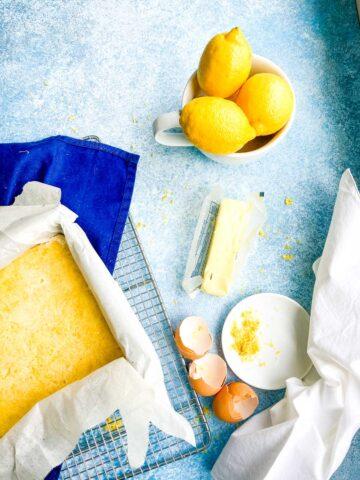lemon bar pan on wire rack with bowl of lemons, a stick of butter, lemon zest and egg shells