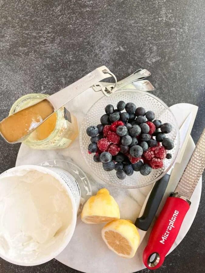 ingredients for frozen yogurt bark: yogurt, honey, berries, lemons on a marble plate