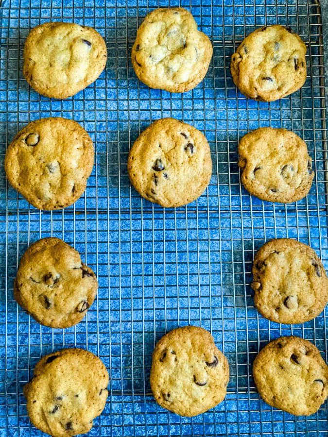 chocolate chip cookies on a wire rack on a blue background