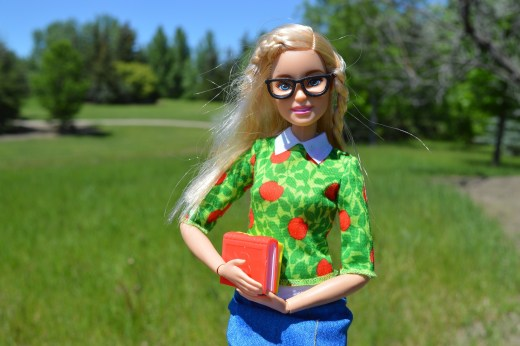 Barbie on a walking path, wearing glasses and holding a school book.