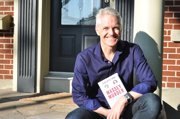 Christopher Deacon displays his copy of The Massey Murder by Ottawa-based author Charlotte Gray as he sits on the front steps of his home on Denbury Avenue. Photo by Adam Feibel.
