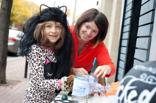 Molly van der Schee, owner of the Village Quite helps Sarah Hope (8), make a ghost lantern. For Molly, the event is about bringing business into the area, making connections, and giving back to customers and friends who support local business and make the community a great place to live and work.