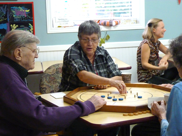 WEBDiana-Potvin-Carefor-volunteer-engaged-with-2-clients-in-a-game-of-Crokinole